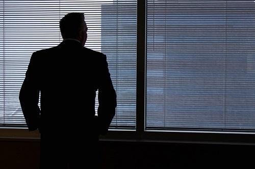 muž přemýšlí u okna